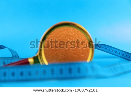 Magnifying glass and orange on a blue background as a symbol of cellulite. Concept Anti-cellulite program. Selective focus. Foto stock ©