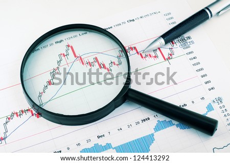 magnifying glass and pen over graph