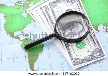 Magnifying glass black frame and currency on world map paper.