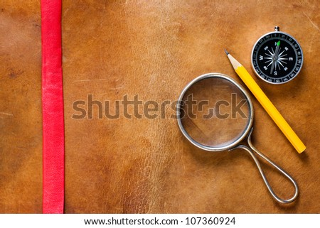 Magnifying glass, compass and pencil on old gunge leather background