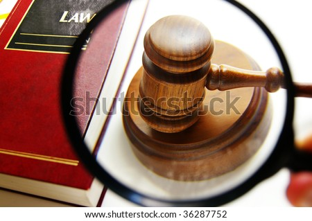 magnifying glass examining a judges court gavel, with law book
