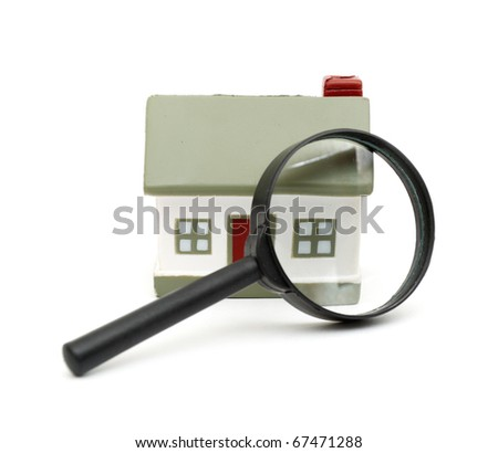 magnifying glass examining model home. Isolated on white.