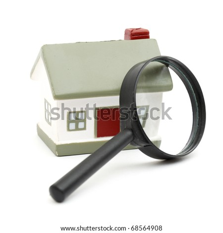 magnifying glass examining model home. Isolated on white. - stock photo