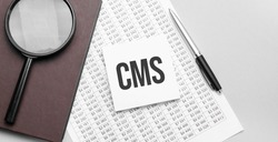 Magnifying glass, financial document, white paper sheet witn CMS sign and brown notebook on grey background.