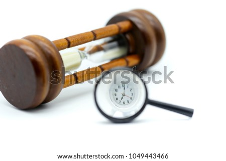 Magnifying glass focusing of Sandglass, hourglass with clock. #1049443466