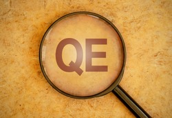 Magnifying glass focusing on QE for quantitative easing