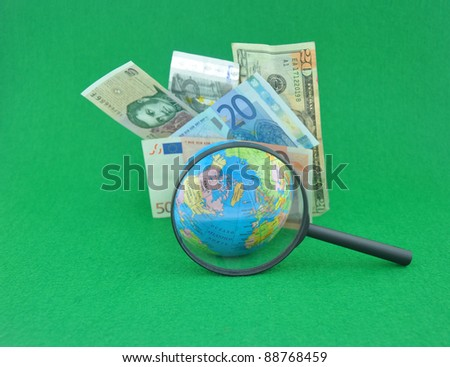 Magnifying Glass Highlighting World Globe in front of International Currency on Green Background