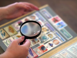 magnifying glass in hand against the background of an album with postage stamps