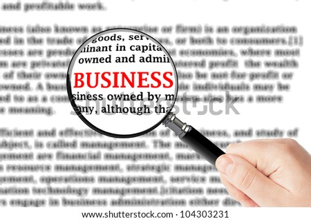 Magnifying glass in hand and business sign