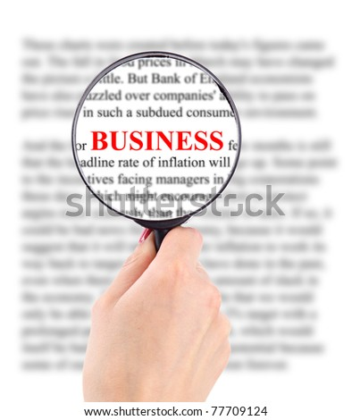 Magnifying glass in hand and word busines