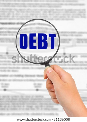 Magnifying glass in hand and word Debt, business background