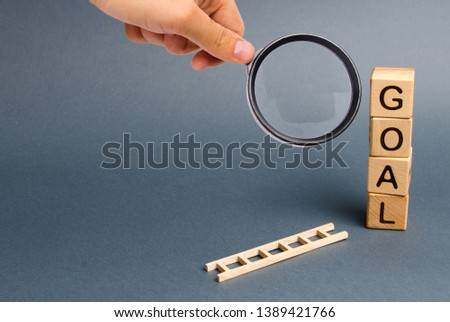 Magnifying glass is looking at a tower of cubes with an inscription goal and a fallen ladder. Tool for success. Don't give up half way. achieving the goal, subject to application of all the efforts