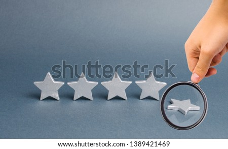 Magnifying glass is looking at five silver stars, one star fell. Loss of rating and level, reducing prestige and reputation. Rating and status of the restaurant or hotel. Prestige and a good title.
