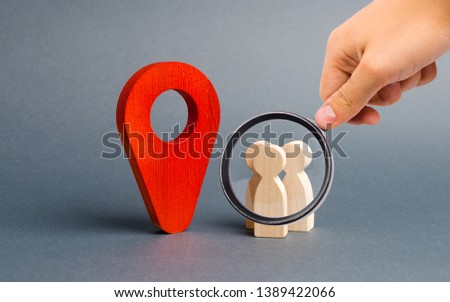 Magnifying glass is looking at people are standing near the location marker. Concept of navigation and venue. Tourism and travel. Orientation around the city, location of events #1389422066