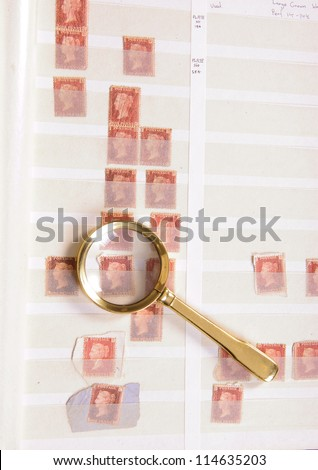 Magnifying glass laying on a philatelic stamp album