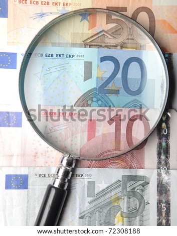 Magnifying glass lying on banknotes