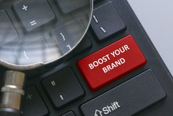 Magnifying glass on a computer keyboard with red button written with advice Boost your brand.