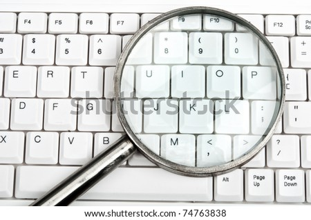 Magnifying glass on an white keyboard - stock photo