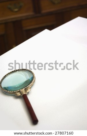 Magnifying glass on blank paper with desk in background.  Customization space for text or document insert.