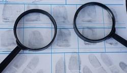 Magnifying glass on fingerprint crime page file.Concept of finding evidence in criminal.