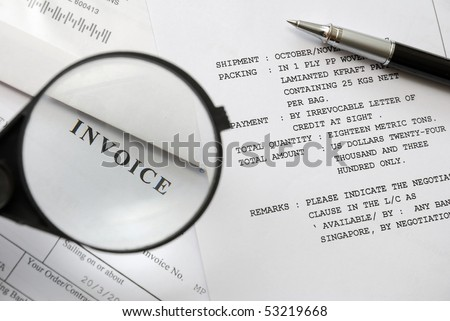 Magnifying glass on invoice text with pen on purchase and sales related documents in background. For business and office life, and sales and purchase concepts.