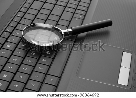 Magnifying glass on laptop computer keyboard - stock photo