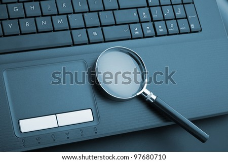 Magnifying glass on laptop computer. Toned in blue