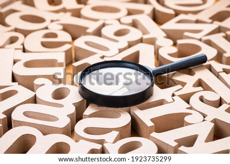 Magnifying glass on many English alphabet wood letters. Keyword searching. Find the right word to communicate. English learning concept