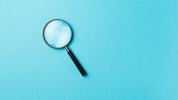 Magnifying glass on pastel background. Top view. Flat lay. Copy space. Minimal creative concept. Blue background in pastel colours