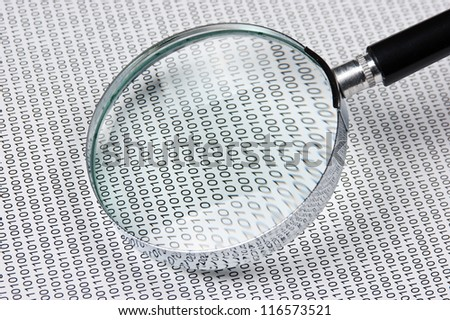 magnifying glass on the background of a binary code