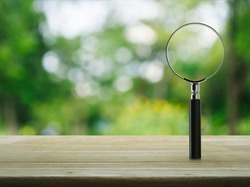 Magnifying glass on wooden table over blur green tree in park, Business analyzing concept