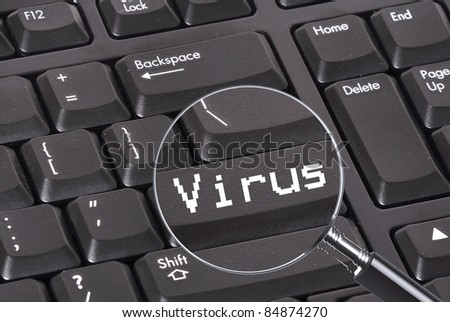 Magnifying glass over a keyboard detecting a virus