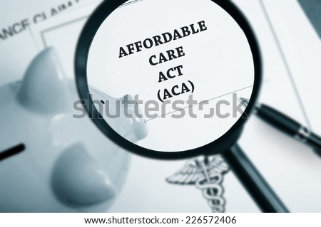 Magnifying glass over Affordable Care Act policy and piggy bank