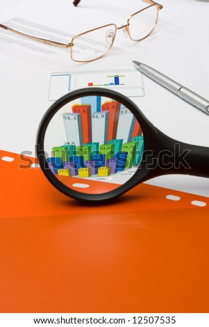 magnifying glass over financial chart and red file - stock photo