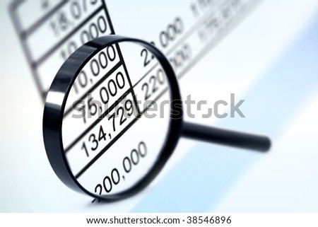 Magnifying glass over financial figures.  Very soft focus.