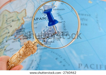magnifying glass over Tokyo, Japan map with destination tack