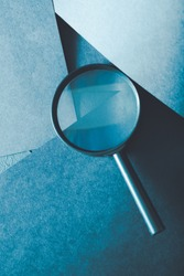 magnifying glass. science research exploration and scrutiny concept. loupe on layered blue paper background.