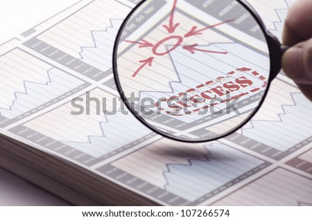 Magnifying glass showing the success on business and stock market.