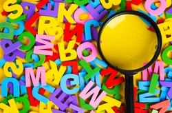 Magnifying glass with colorful alphabet on yellow background.Education concept.
