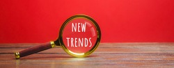 Magnifying glass with the inscription New Trends. The concept of searching for new ideological trends and tendencies. Exclusive trend. Popular and relevant topics.