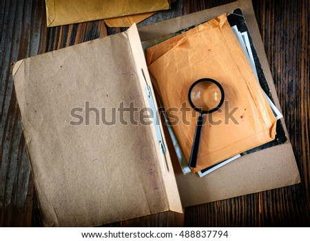 Magnifying glass with vintage documents retro investigation spy discovery concept