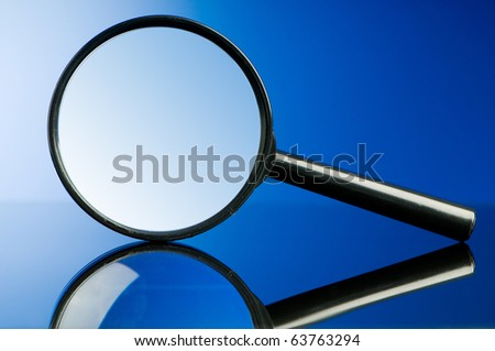 Magnifying glass with wooden handle on the flat surface