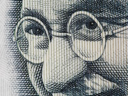 Mahatma Gandhi face on indian 100 rupee banknote extreme macro, India money closeup