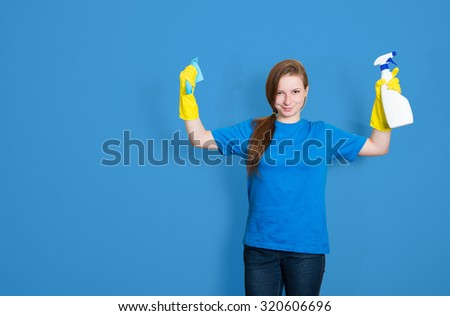 Maid cleaning woman with cleaning spray bottle. Cleaning service. Portrait of beautiful cleaning girl isolated on blue background with copyspace. Mixed race woman.