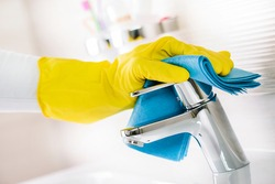 Maid hand or charwoman cleaning modern new basin in bathroom, water tap clean using yellow gloves and blue cloth.