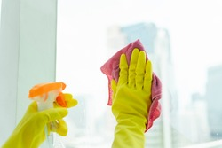 Maid hand wearing yellow gloves cleaning glass mirror using detergent spray bottle and rack cloth. House cleaning. Covid-19 Coronavirus prevention.