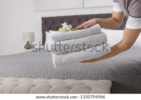 Maid holding fresh towels with flowers in hotel room, closeup #1330794986