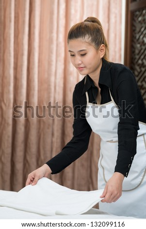 Maid holding towels in a hotel