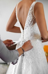 Maid of Honour helping the bride to dress in her elegant white wedding gown tying the bow at the back in a close up on her hands