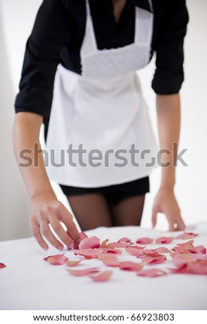 Maid preparing heart with petals on honeymooners' bed
